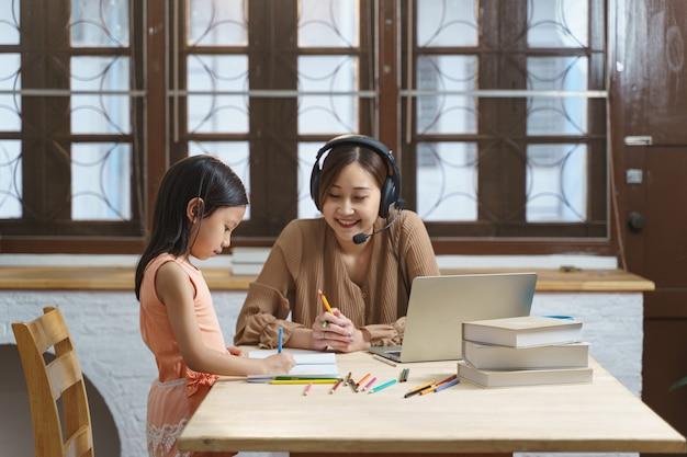 집에서 어머니와 함께 거실에서 숙제와 공부, 독서를 하는 아시아 홈스쿨 소녀