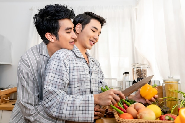 Asian homosexual couple happy and funny cooking salad at kitchen.concept lgbt gay.