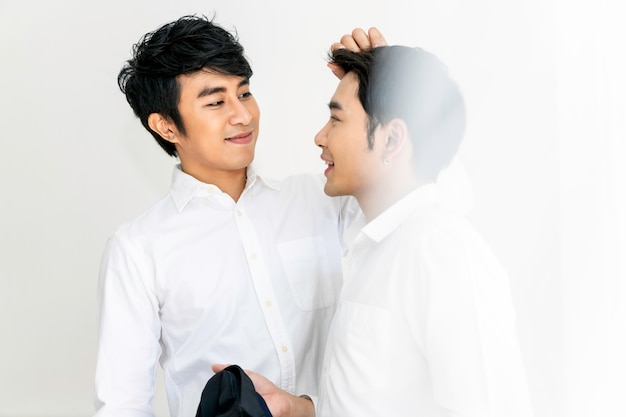 Asian homosexual couple helping each other dress up.