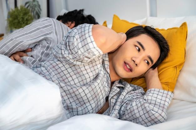 いびきをかくと寝室で寝ているパジャマでアジアの同性愛カップル。彼は手で耳をブロックします。概念lgbtゲイ。