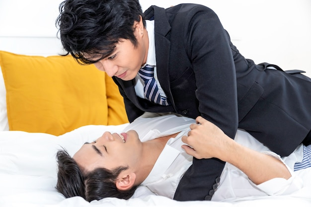 Asian homosexual couple in love looking into each others eyes in the bed