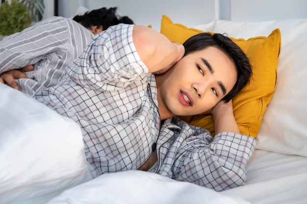 Asian homosexual couple in pajamas snoring and bad sleeping on the bedroom.he blocking ears with hands