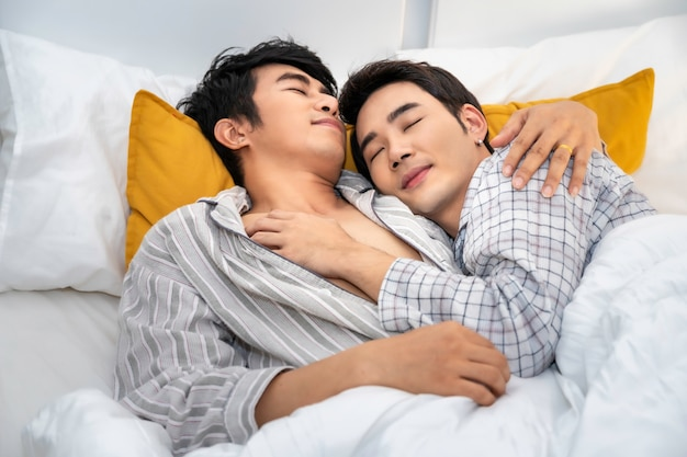 Asian homosexual couple in pajamas sweet dream and sleeping on the bedroom