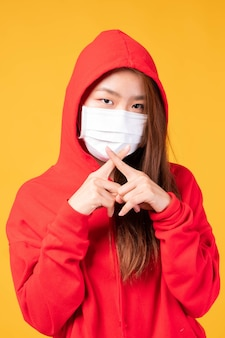黄色の背景での検疫コロナウイルスcovid19の発生中に保護のための保護フェイスマスクを身に着けているアジアのパーディーの女の子は、拡散covid-19とpm2.5大気汚染を保護します