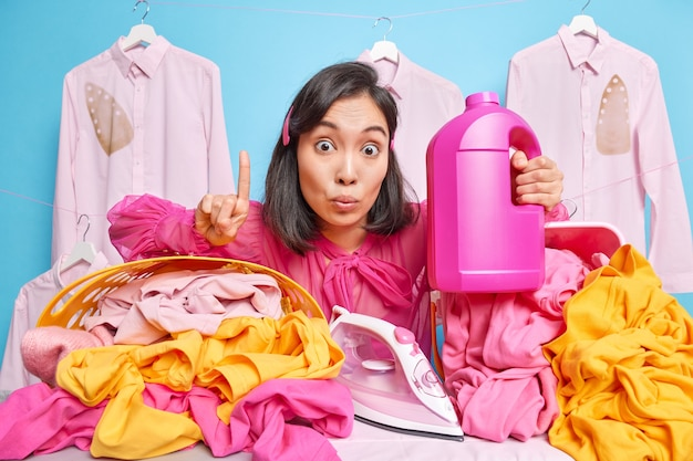 Asian housekeeper keeps index finger raised up holds detergent bottle going to iron laundry after washing gets excellent idea spends much time of domestic work