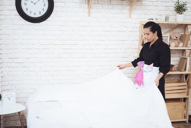 Asian housekeeper makes bed in modern apartment