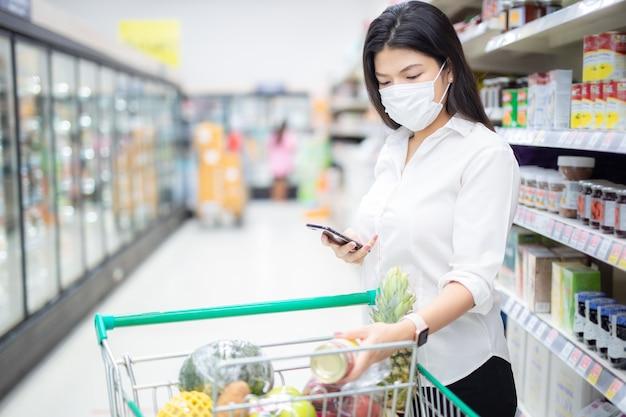 スマートフォンでアジアの主婦チェックリストとマスク付きの買い物で食料品、スーパーでの安全対策。