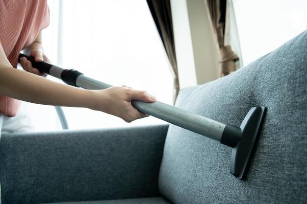 아시아 주부는 거실에 있는 소파를 청소하기 위해 무선 진공 기계를 사용합니다. 거실에서 진공 청소기로 청소하는 아시아 가정부. 집안일 및 일일 가사 활동 개념입니다.