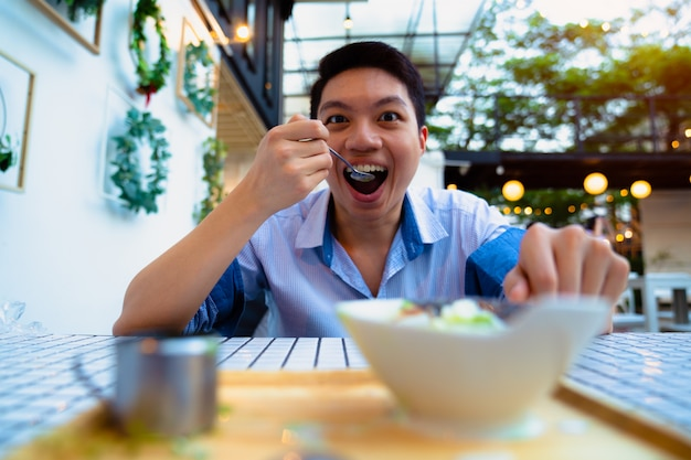 Asian hungry man eating cereal for breakfast looking at camera.