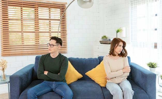 アジアの夫と妻が自宅のリビングルームのソファで主張し、怒っています。家族の家事問題。
