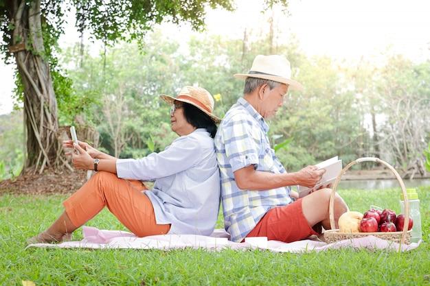 아시아 인 남편과 아내가 앉아서 피크닉을하고 공원에서 휴식을 취하십시오.