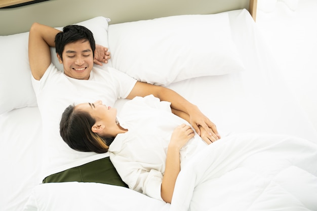 Asian husband and wife relaxing on the bed together in the morning.