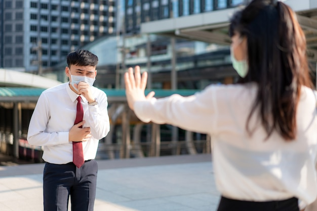 Asian ill businessman cough with mask and businesswoman stop sign hand him to keep distance protect from covid-19 viruses and people social distancing for infection risk