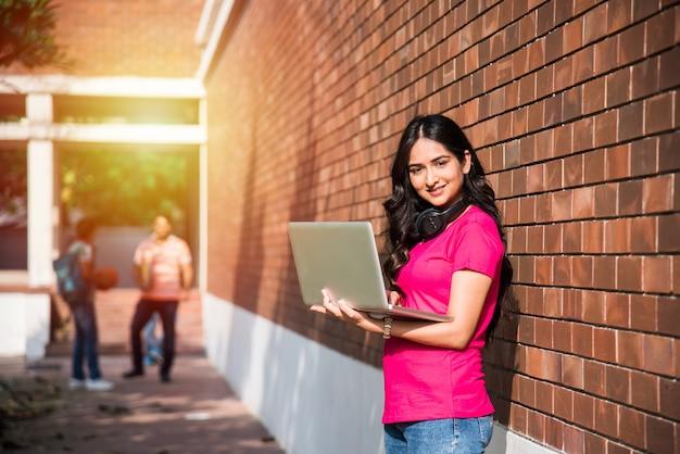 バックグラウンドで他のクラスメート、大学のキャンパスで屋外の写真をしながら、ラップトップや本を読んで作業に焦点を当てているアジアのインドの大学生