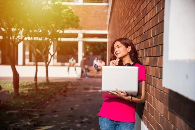 백그라운드에서 다른 급우, 대학 캠퍼스의 야외 사진 동안 노트북에서 작업하거나 책을 읽는 데 초점을 맞춘 아시아 인도 대학생
