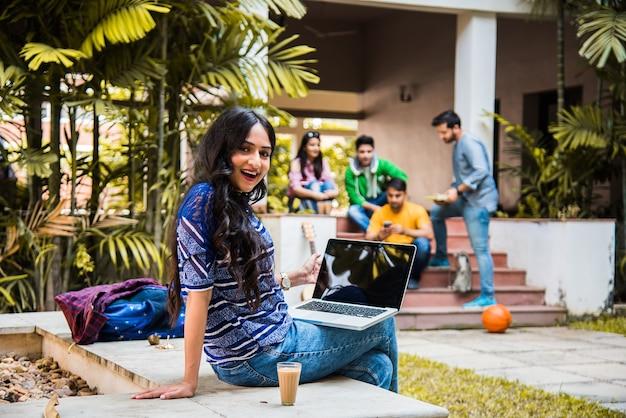 Азиатский индийский студент колледжа в фокусе работает за ноутбуком или читает книгу, в то время как другие одноклассники на заднем плане, фотография на открытом воздухе в университетском городке