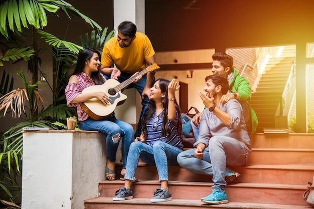 階段や芝生の上にキャンパスに座ってギターで音楽を演奏するアジアのインドの大学生