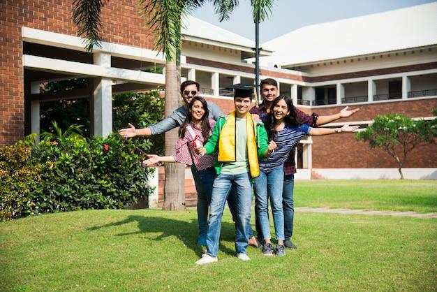 友人が屋外の大学のキャンパスで祝う間、アジアのインドの大学生は学位証明書を受け取ります