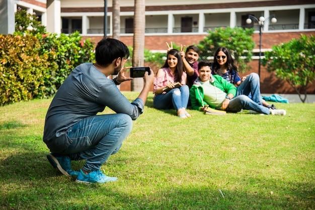 階段や芝生に座って楽しんでいる間、キャンパスでスマートフォンを使用して自分撮り写真を撮るアジアのインドの大学生