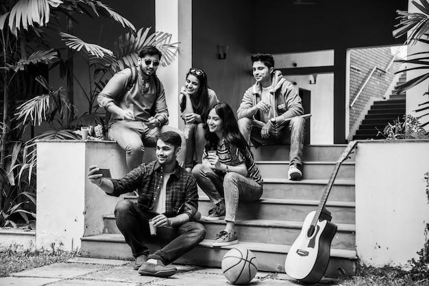 Азиатские индийские студенты колледжа делают селфи с помощью смартфона в кампусе, сидя на лестнице или лужайке, весело