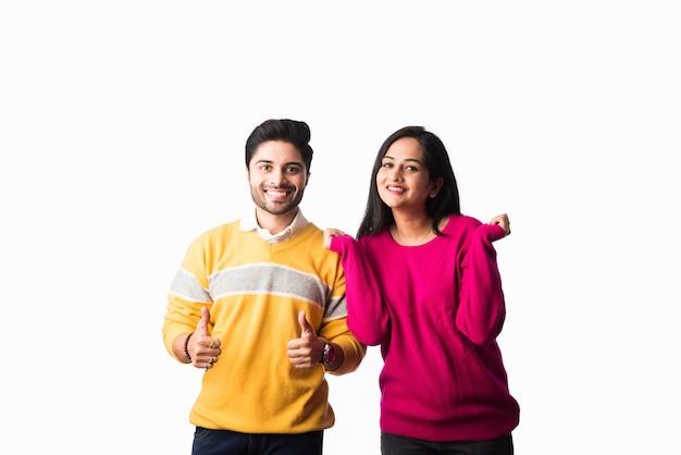 アジアのインドのカップルは、白い背景に対して隔離されて立って、カラフルな暖かいセーターまたはウールの冬の布を着ています