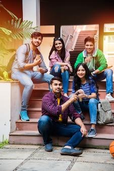 Азиатская индийская группа студентов колледжа пьет кофе во время перерыва в помещении кампуса на открытом воздухе. болтать
