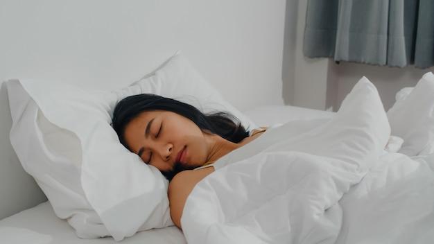 アジアのインドの女性は、自宅の部屋で寝ます。幸せを感じている若いアジアの女の子は、ベッドに横になっている残りをリラックス、朝の家の寝室で快適で落ち着いた感じ。