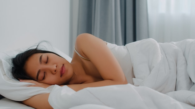 Asian indian lady sleep in room at home. young asian girl feeling happy relax rest lying on bed, feel comfortable and calm in bedroom at house at the morning.