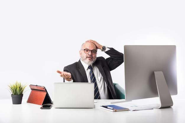 그의 워크 스테이션 또는 책상 컴퓨터, 노트북 및 태블릿 앞에 앉아 아시아 인도 수석 금융 사업. 서류 작업을하는 동안 전화로 말하기