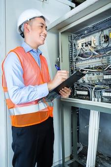 Азиатский индонезийский техник или электрик, выполняющий функциональные испытания коробки выключателя или распределительной коробки с линиями электропередач на строительной площадке или на заводе для приемки
