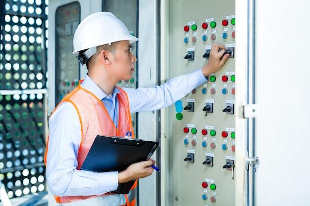 Азиатский индонезийский техник или электрик, производящий функциональную проверку панели или распределительной коробки для управления кондиционерами на строительной площадке или на заводе для приемки
