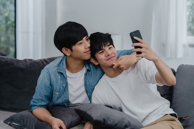 Asian influencer gay couple vlog at home. asian lgbtq men happy relax fun using technology mobile phone record lifestyle vlog video upload in social media while lying sofa in living room .