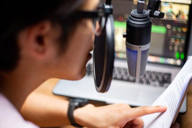 ポッドキャストにマイクを使用し、システムにファイルをアップロードするために音声を録音するアジアの影響力者。ライブ録音。モバイルでオンラインで話す。スタジオオーディオ放送。