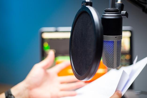 팟캐스트용 마이크를 사용하고 시스템에 파일을 업로드하기 위한 녹음 사운드를 사용하는 아시아 인플루언서. 라이브 녹음. mobile.studio 오디오 방송을 통한 온라인 말하기.