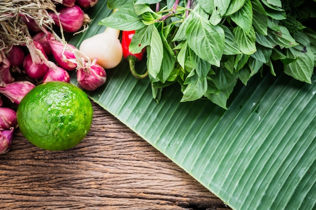 Asian ingredient herb and spicy on wooden table with banana leaf background