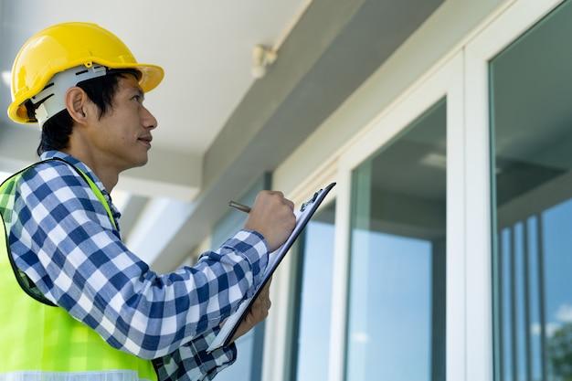 아시아 검사관은 새 건물의 구조를 검토하고 고객에게 판매하기 전에 집을 검사하고 수정하기 위해 클립 보드에 메모를 작성하고 있습니다.