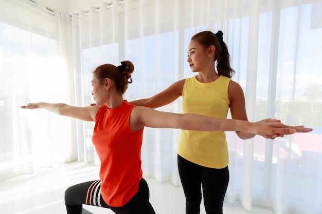 ライトスタジオでのヨガセッション中にウォリアーポーズをしている女性の新人学生をサポートするアジアのインストラクター