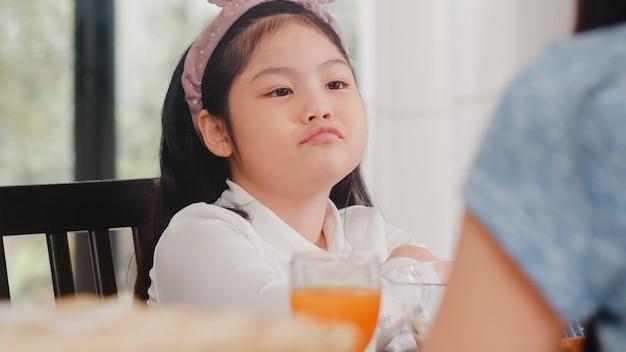 아시아의 일본인 딸은 음식에 지루했다. 라이프 스타일 아이 슬픈 싫어하는 음식 아침에 집에서 현대 부엌에서 아침 식사를 화나게했다.