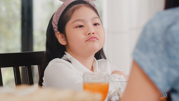 Asian japanese daughter bored with food. lifestyle kids sad dislike food upset breakfast meal in modern kitchen at house in the morning .