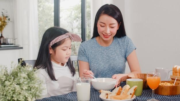 アジア系の日本人家族は家で朝食をとります。アジアの母と娘が一緒に幸せな話をしながらパンを食べて、オレンジジュース、コーンフレークシリアル、牛乳をモダンなキッチンのテーブルの上の朝に飲みます。