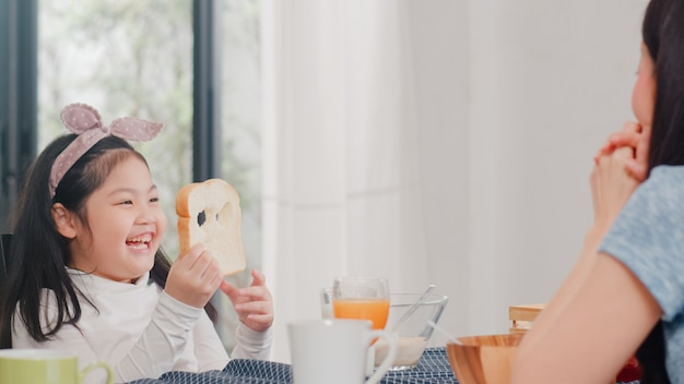 Asian japanese family has breakfast at home. asian daughter pick and play bread laughing smile with parents while eating corn flakes cereal and milk in bowl on table in modern kitchen in the morning.