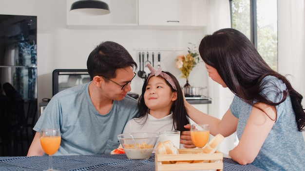 Asian japanese family has breakfast at home. asian mom, dad, and daughter feeling happy talking together while eat bread, corn flakes cereal and milk in bowl on table in the kitchen in the morning.