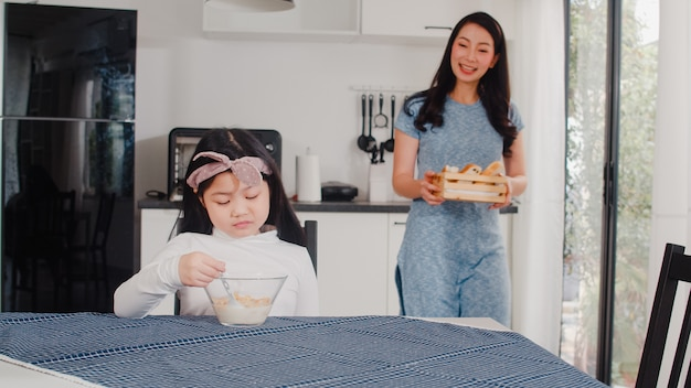 Asian japanese family has breakfast at home. asian mom and daughter feeling happy talking together while eat bread, corn flakes cereal and milk in bowl on table in modern kitchen at house in morning.