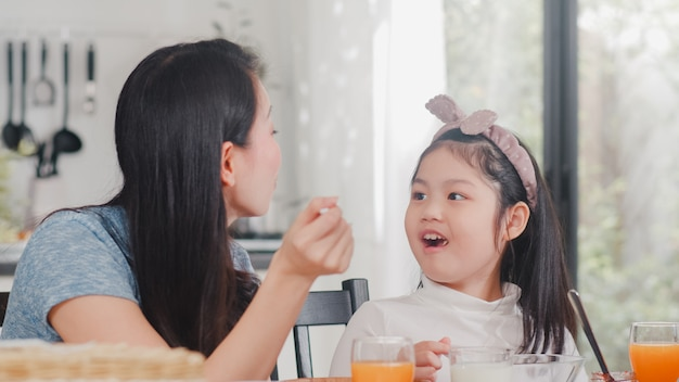 Asian japanese family has breakfast at home. asian mom and daughter happy talking together while eating bread, drink orange juice, corn flakes cereal and milk on table in modern kitchen in morning.