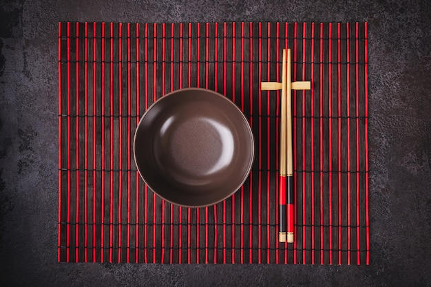 Asian japanese table setting. bamboo chopsticks and bowl on striped mat.