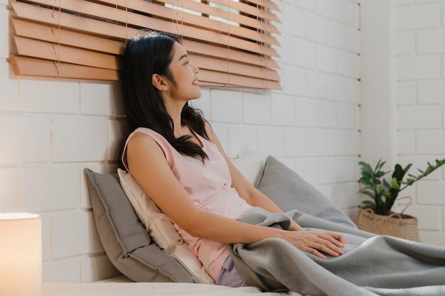 아시아의 일본 여성이 집에서 일어난다.