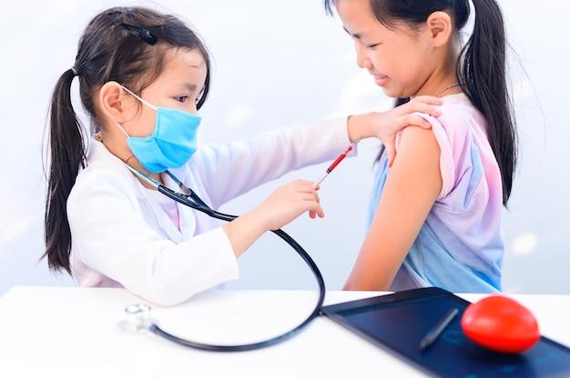 医者とヘルスケアの概念としてのアジアの子供。ウェルネスとセルフケア。子供たちは、コロナウイルスを止めるのを助けるために成長したときに仕事を夢見ます。