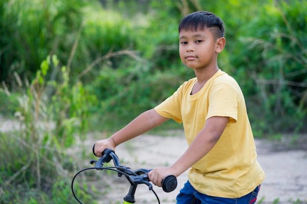 Asian kid boy ride bicycle in nature