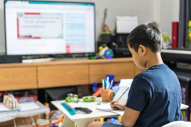 Asian kid distance learning online education with smart tv