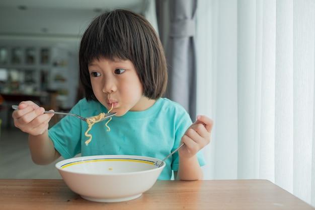 麺を食べるアジアの子供